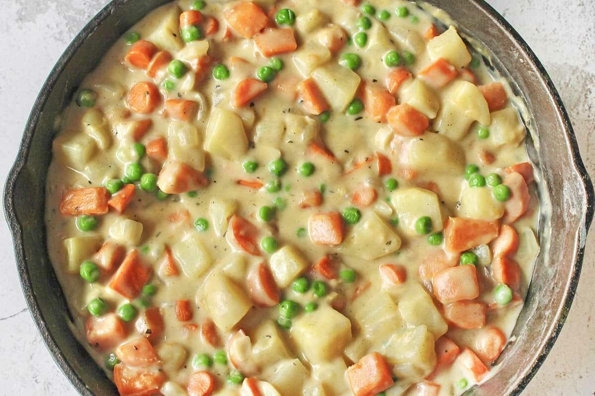 Овощная запеканка. начинка из картофеля, гороха и моркови в чугунной сковороде.