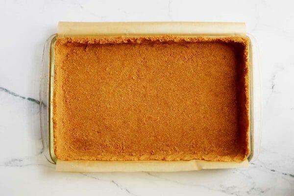 Батончики из тыквенного пирога с коркой крекера Грэма, запрессованные в стеклянную форму для выпечки, выложенную пергаментом.