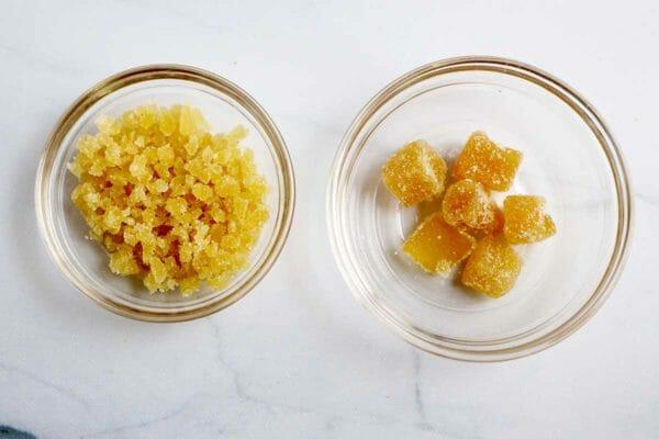 Цукаты из имбиря нарезать в одной миске и нарезать кубиками в другой, чтобы приготовить Лучший рецепт батончика с тыквенным пирогом.