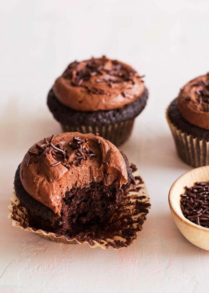 Кексы с шоколадной глазурью с вынесенным кусочком и на прилавке.