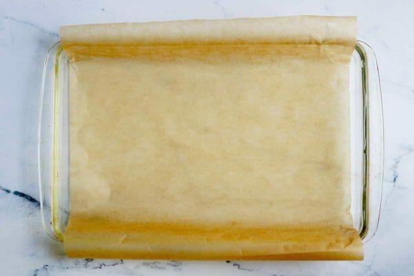 Форма для выпечки, выложенная пергаментной бумагой, чтобы показать, как чтобы приготовить батончики для тыквенного пирога.