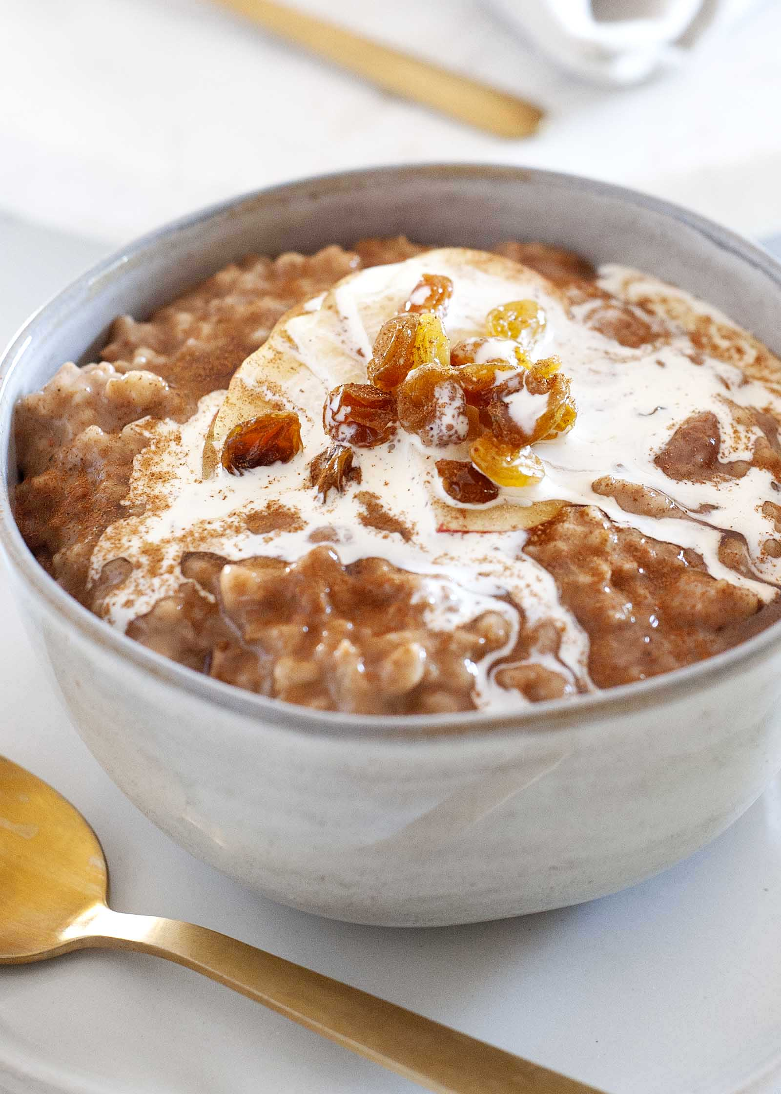Crockpot Oatmeal, покрытый сверху молока и золотого изюма с золотой ложкой внизу.