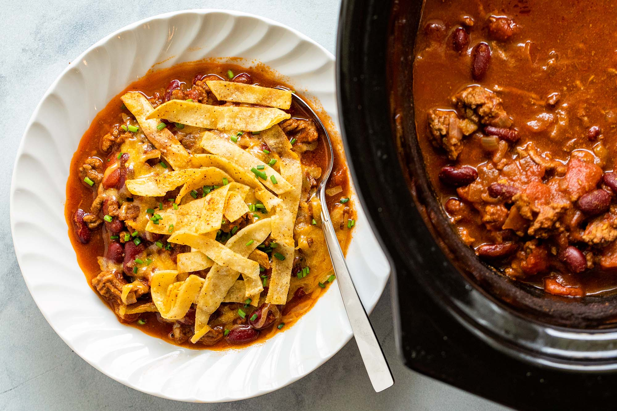 Easy Slow Cooker Beef and Bean Chili, покрытые жареными ножками из тортильи в белой миске. Мультиварка находится справа от миски.