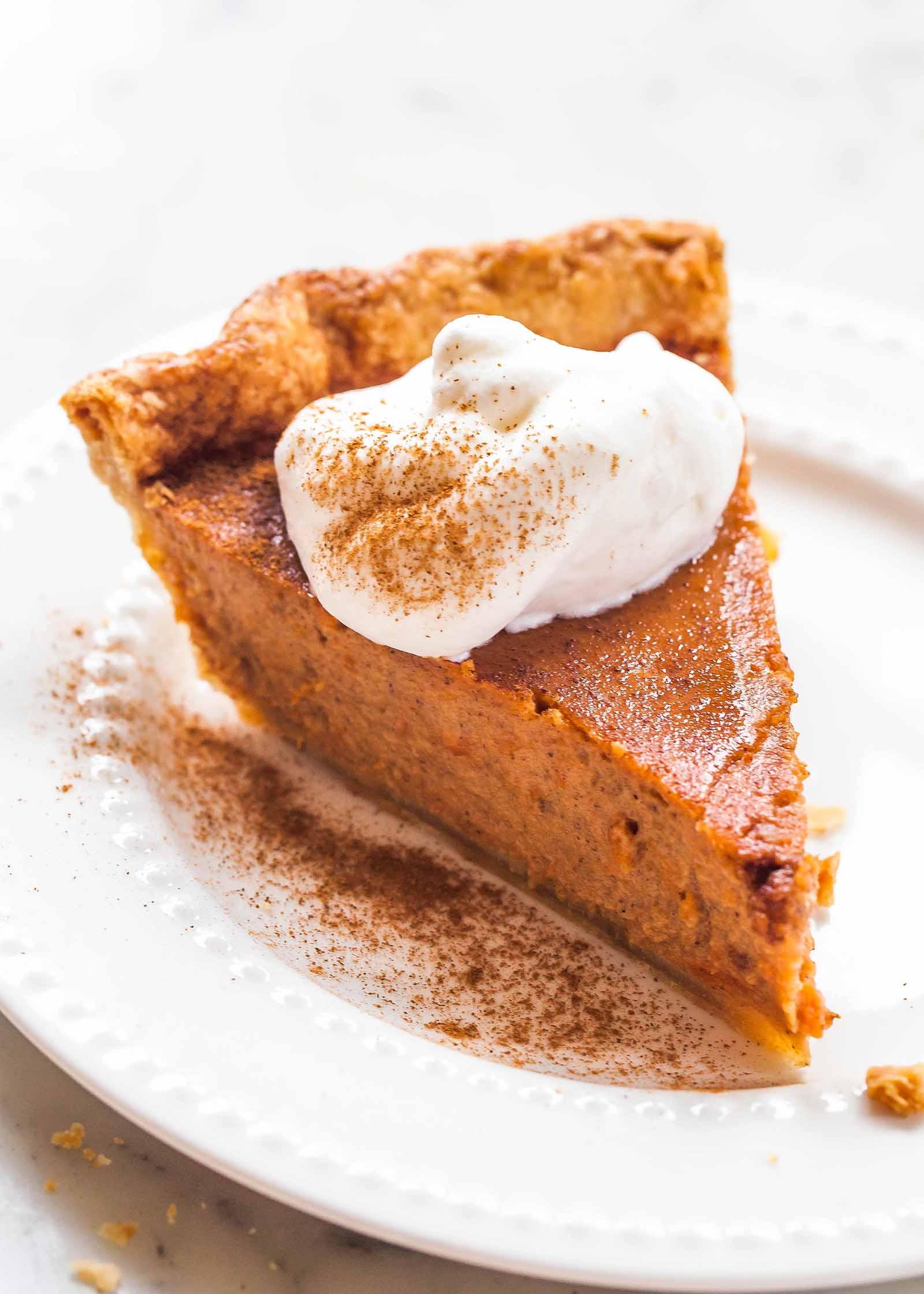 Ломтик пирога из сладкого картофеля на белой тарелке со взбитыми сливками посыпанный корицей и вилкой.