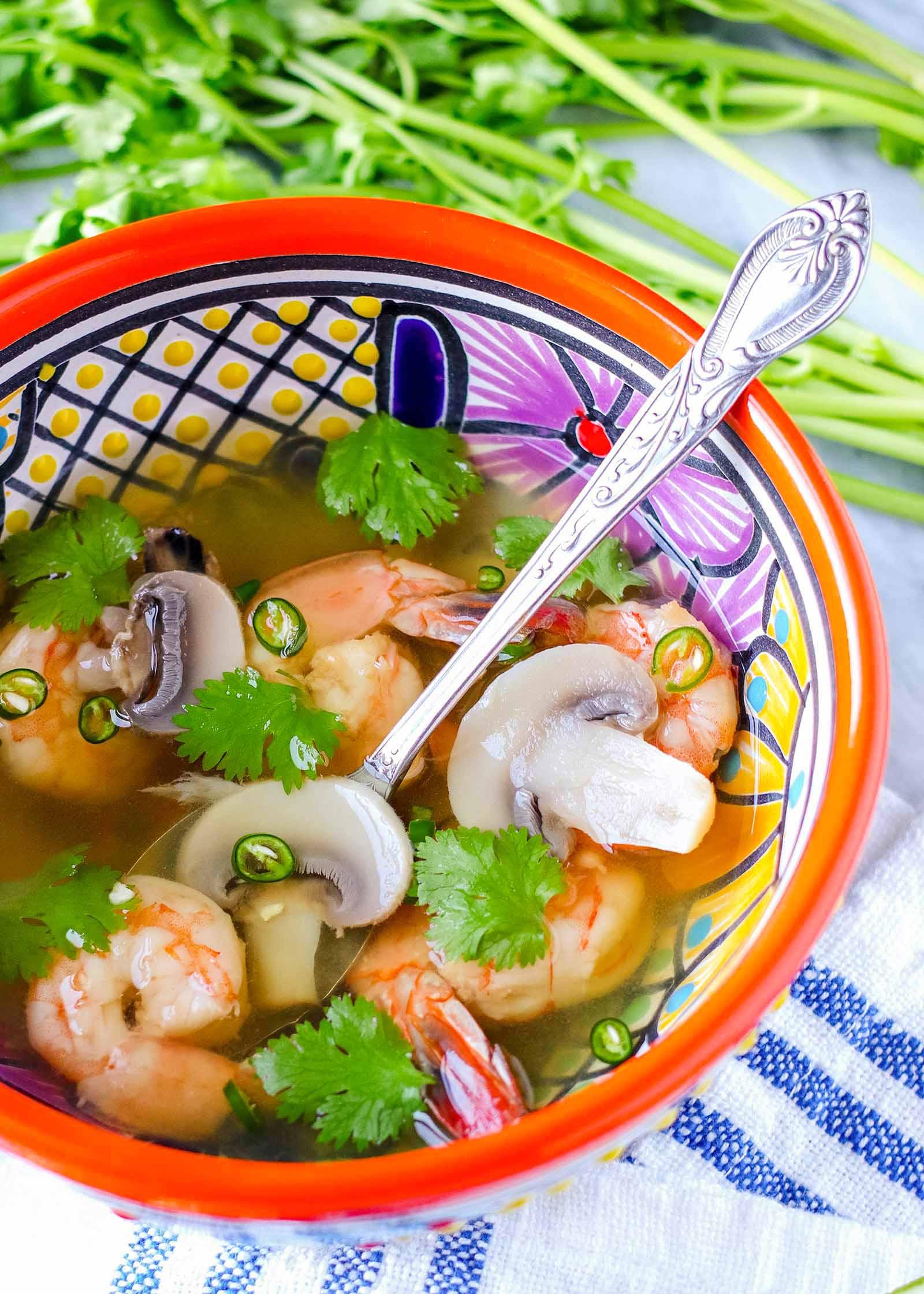 Вертикальный вид чаши с ярким рисунком и серебряной ложкой внутри. В миске суп Том ям с креветками, кинзой и грибами на легком бульоне. Над чашей - стебли кинзы, а под чашей - льняное полотно в синюю полоску.