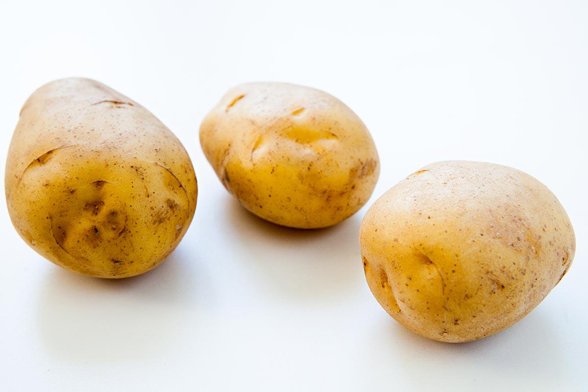 Три золотых картофеля Юкона на белой поверхности