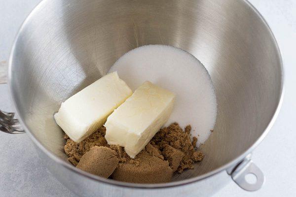Сливочное масло, сахар и коричневый сахар в металлической чаше для легкого рецепта шоколадного печенья.