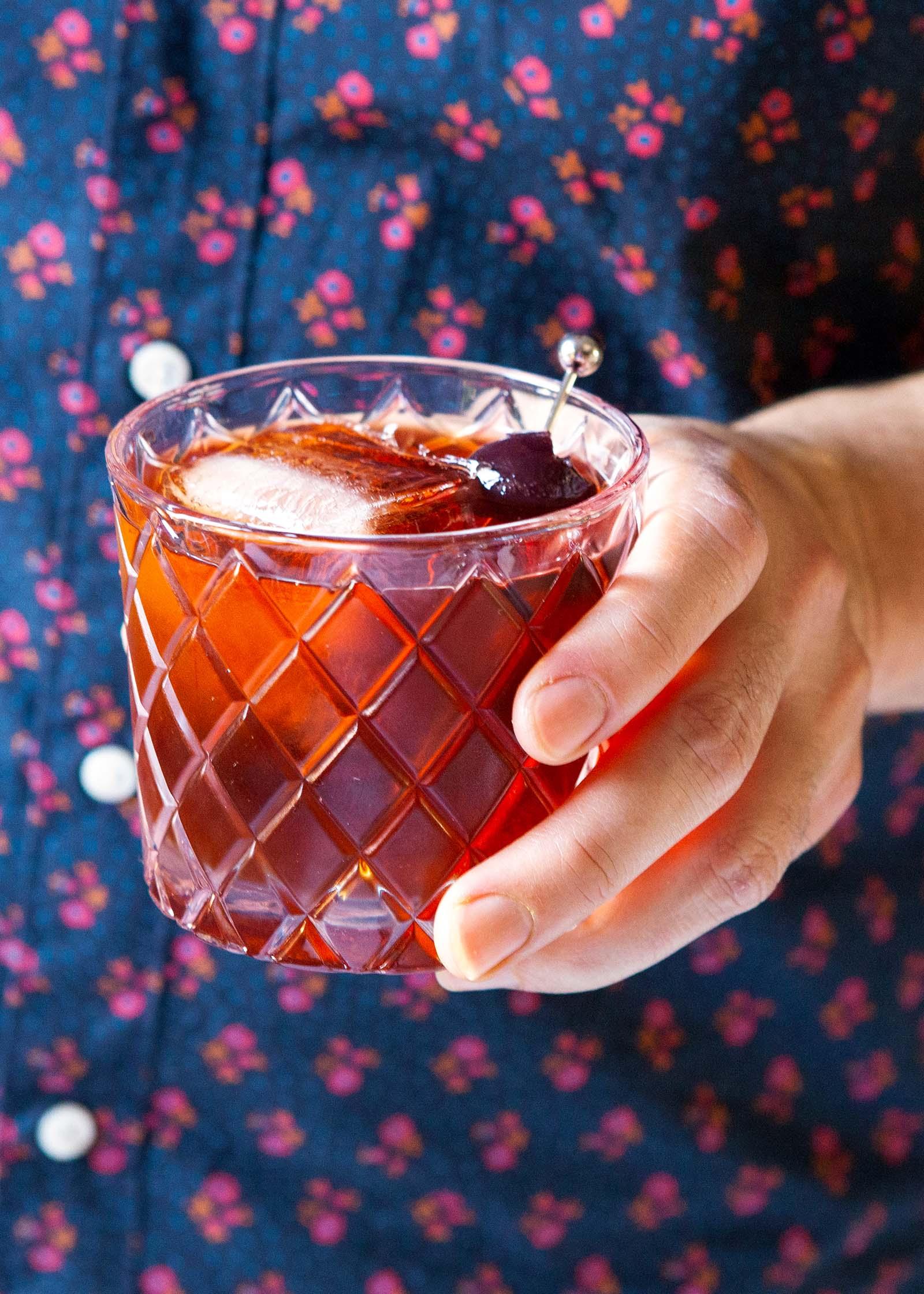 Vieux carre с квадратными кубиками льда и вишневым гарниром держится в руке человека.