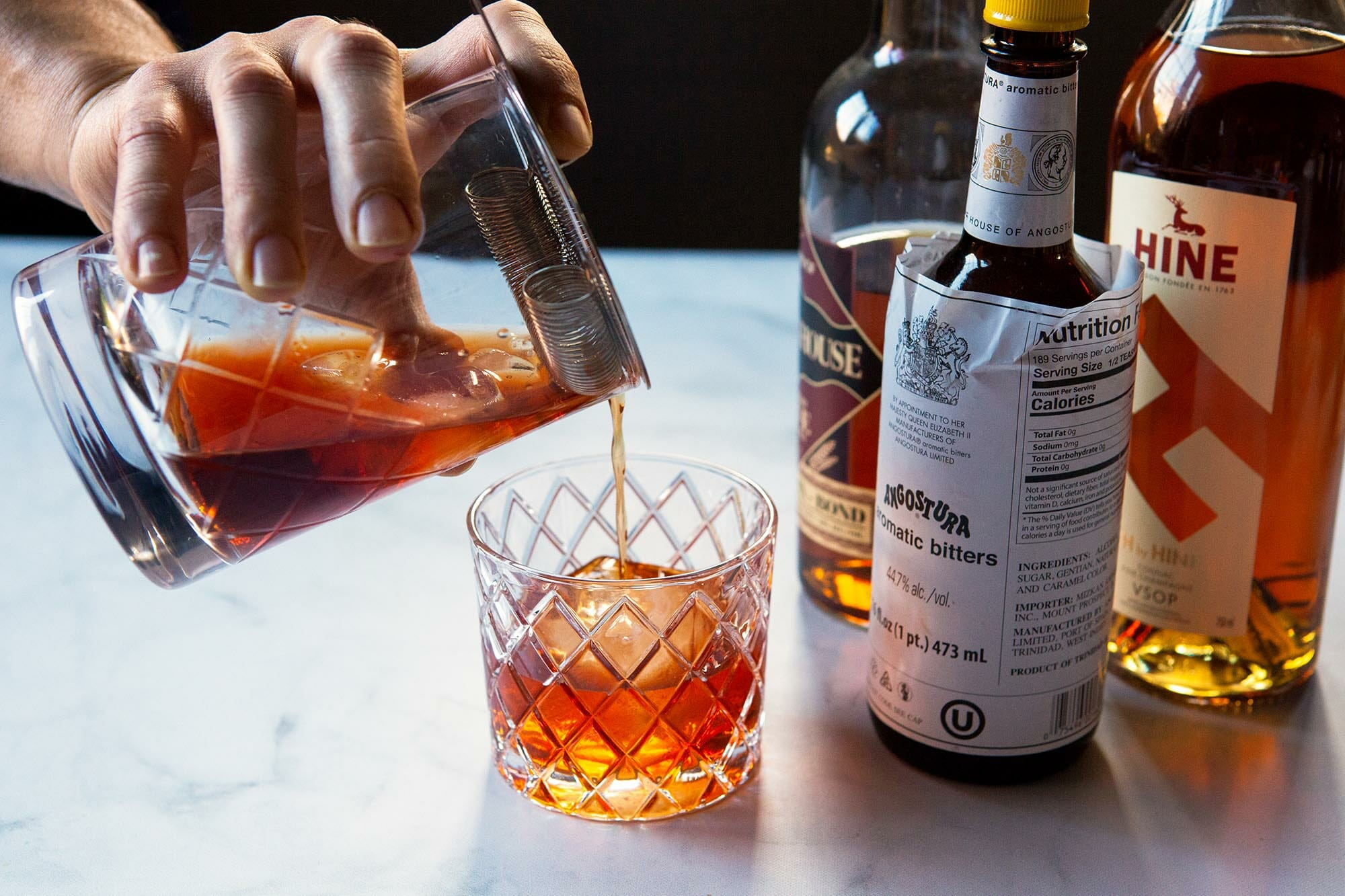Vieux carre процеживают в бокал для виски. Бутылки для коктейля - справа.