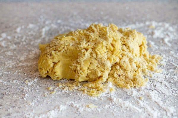 Тесто для рождественского печенья Butterhorn, брошенное на посыпанный мукой прилавок.