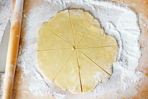 Круг теста, раскатанный на посыпанной мукой столешнице, разрежьте на треугольники, чтобы приготовить печенье Butterhorn с начинкой из грецких орехов.