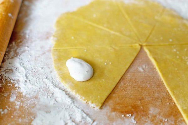Начинка внутри треугольника из теста, чтобы сделать венгерские рожки для масла.