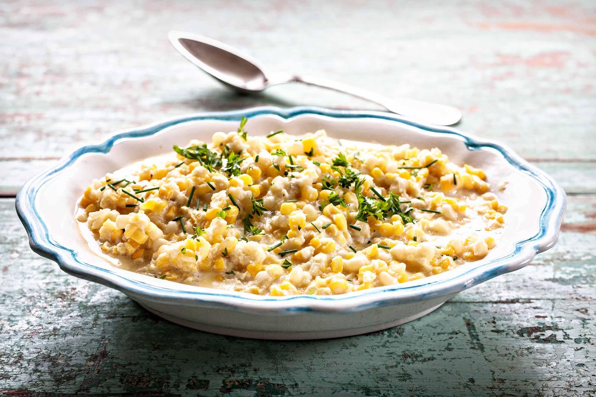 Лучший рецепт кремовой кукурузы - чаша кремовой кукурузы с ложкой и зеленью