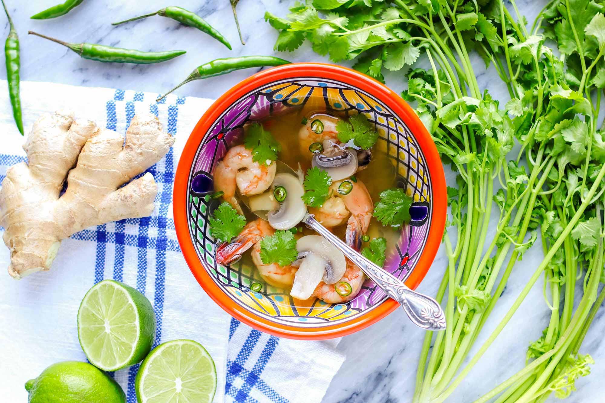 Тайский суп с креветками в миске с ярким рисунком и серебряной ложкой внутри. Нарезанный лайм, имбирь, перец и стебли кинзы окружают чашу с легким бульоном, креветками, грибами и кинзой. Чаша стоит на мраморной стойке с льняной тканью в синюю полоску слева от чаши.