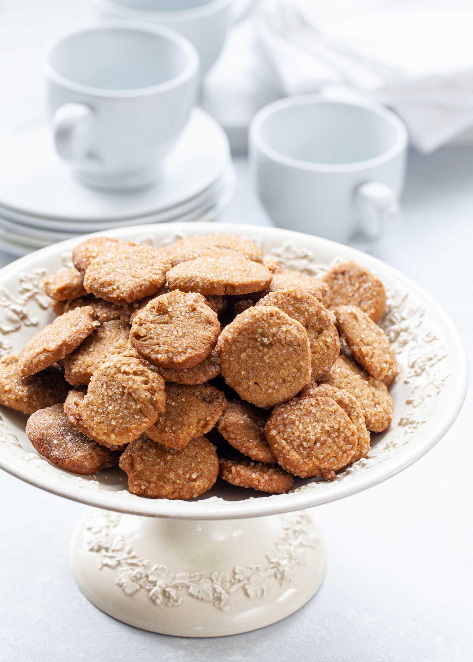 Make Ahead Slice и Выпекайте имбирное печенье с горкой на подставке для торта с кофейными кружками и тарелками для десертов, установленными позади.