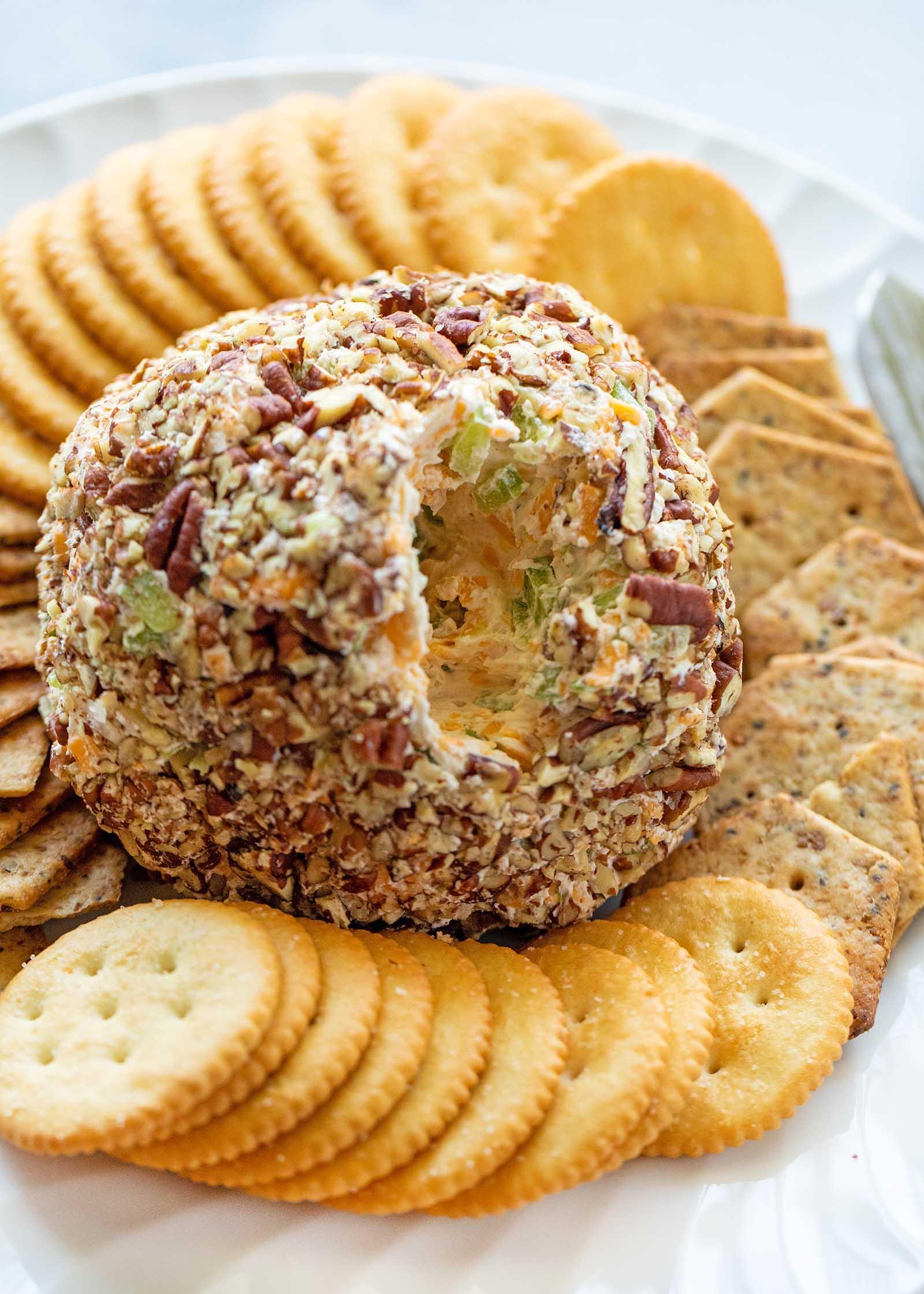 На фото изображен самодельный сырный шарик с вычерпанным кусочком. Крекеры повсюду вокруг сырного шарика.