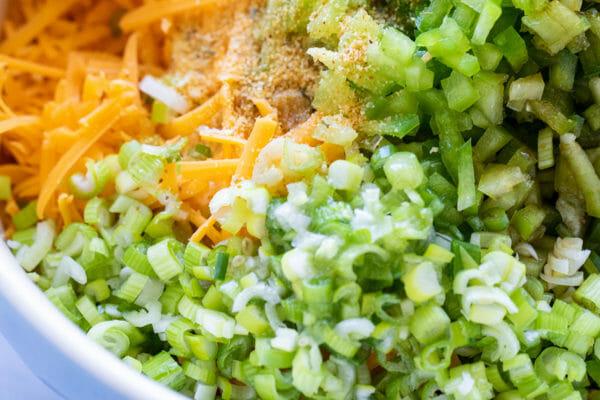 Крупным планом вид нарезанного зеленого лука, измельченного зеленого перца и тертого сыра, чтобы получился легкий сырный шарик.