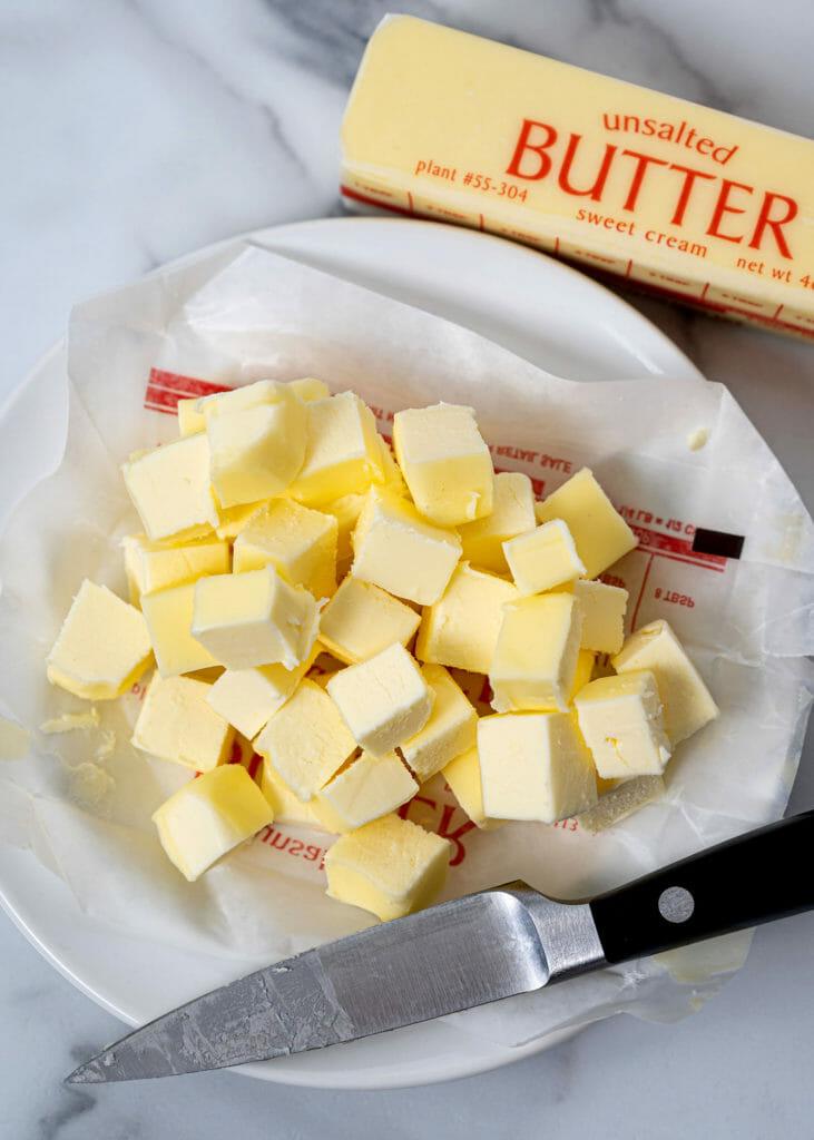 Несоленое масло и тарелка нарезанного кубиками масла
