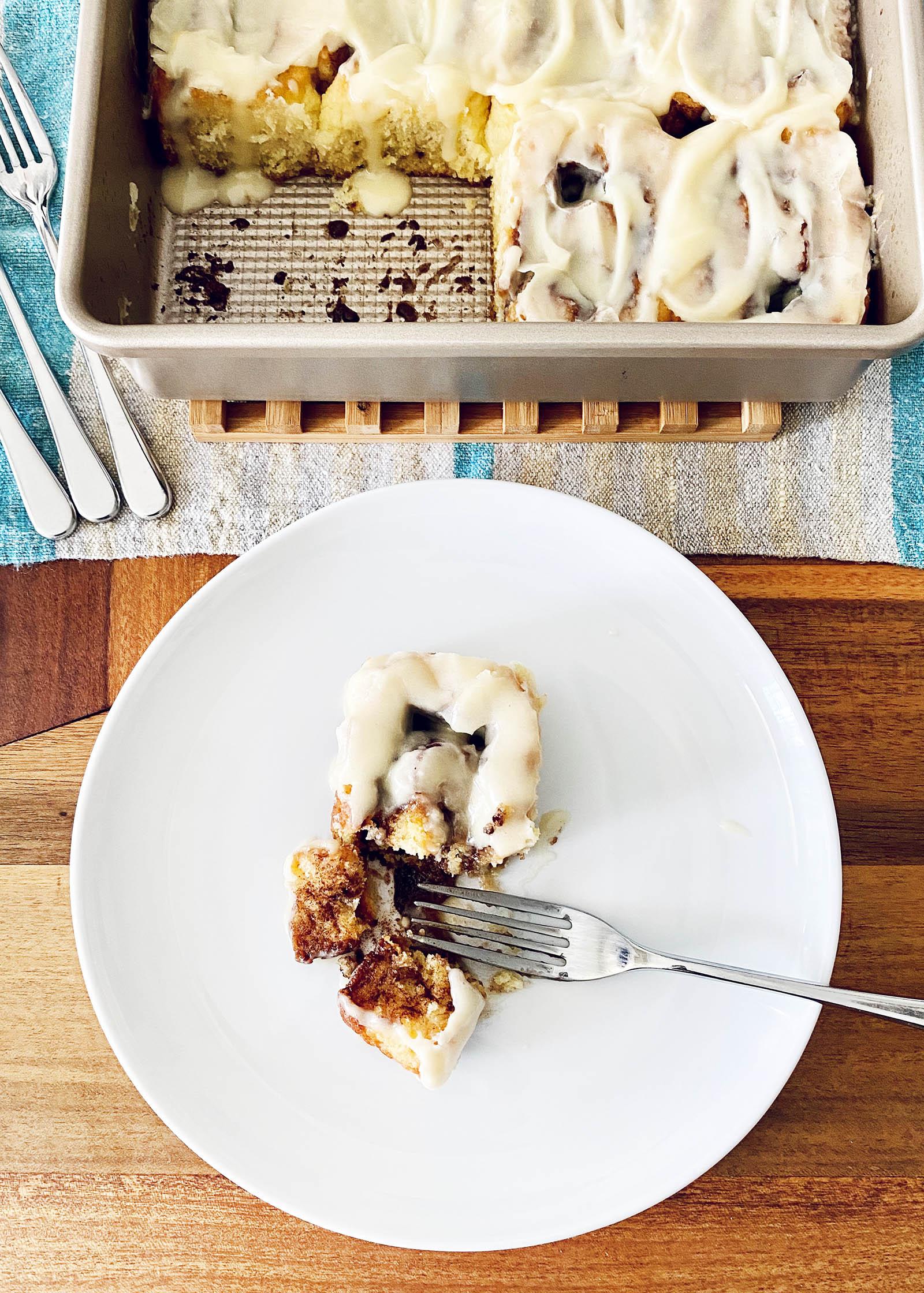 Тарелка с лучшими булочками с корицей без глютена и сковородой с остальными замороженными булочками за тарелкой.