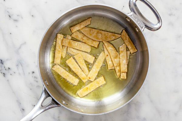 Жарить полоски тортильи в масле для рецепта супа из куриной тортильи
