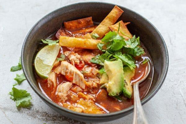 Суп из куриной тортильи подается в миске с ложкой, заправленный чипсами из тортильи, лаймом и кинзой