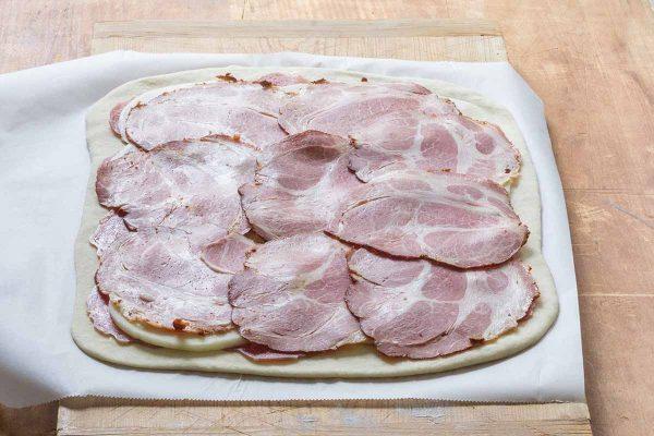 Выложите мясо на тесто для пиццы для стромболи