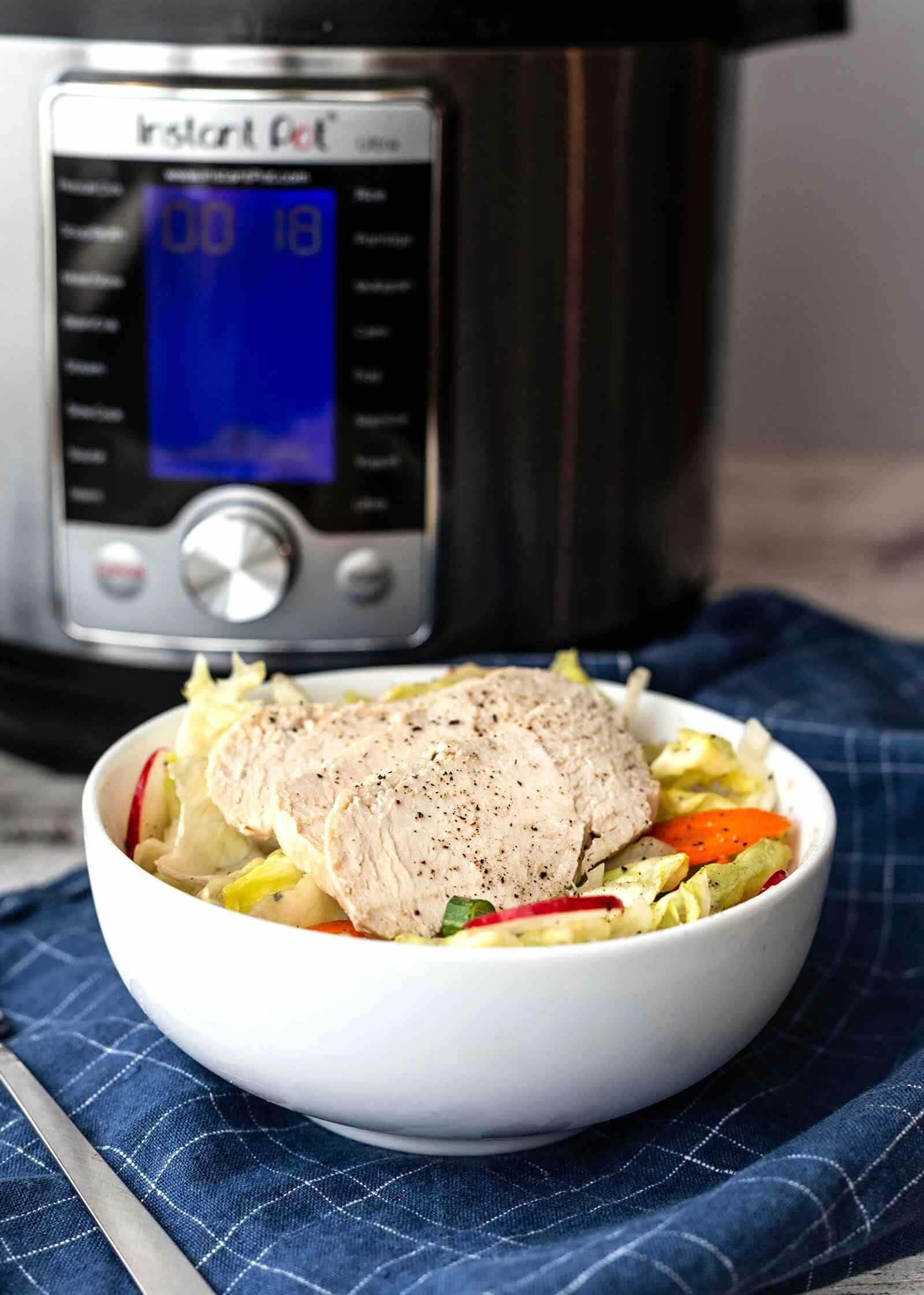 Цыпленок быстрого приготовления, нарезанный и поданный с салатом, на фоне горшок быстрого приготовления