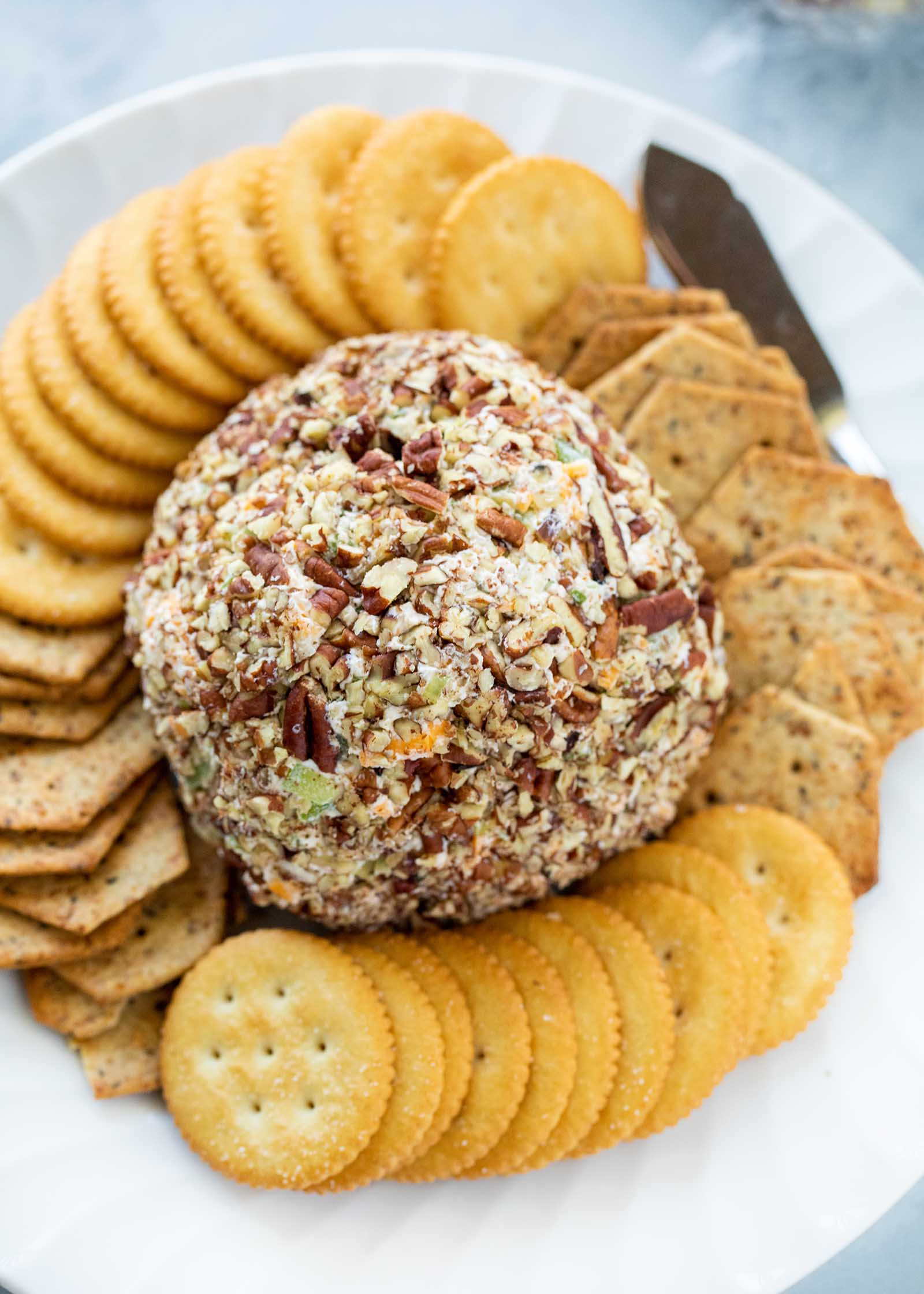 Классический сырный шарик в центре тарелки, окруженный крекерами.