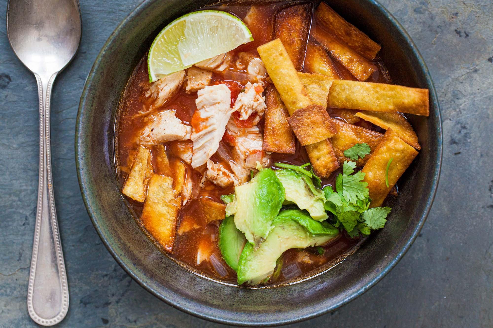 рецепт супа из куриных лепешек, который подается в миске и покрывается лаймом, авокадо, кинзой и другие начинки.