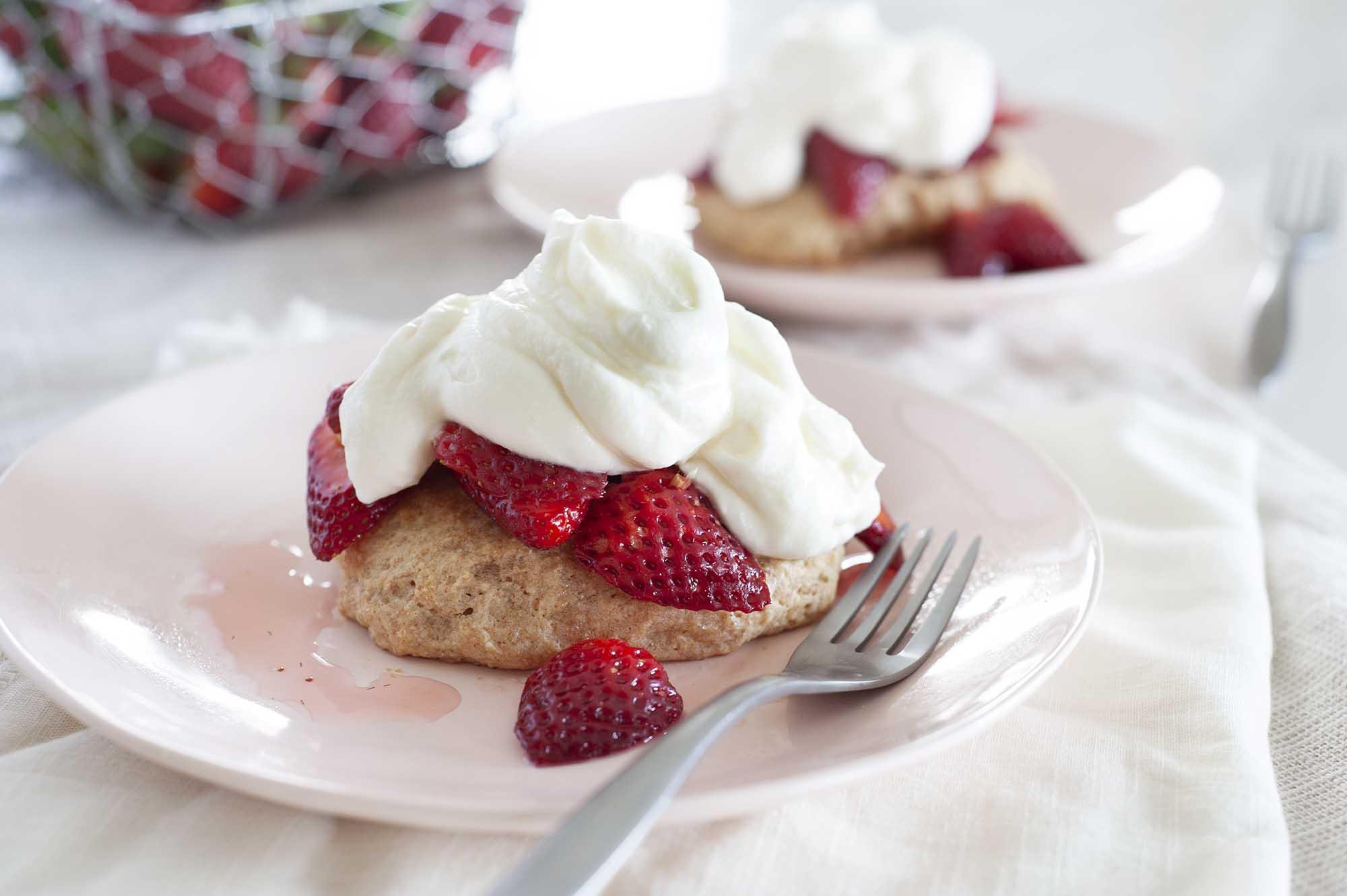 Две тарелки с легким клубничным пирогом, поставленные на стол с белым постельным бельем. Песочное печенье выложено нарезанной клубникой и начинкой из взбитого йогурта. Слева от тарелок находится проволочная корзина с клубникой.