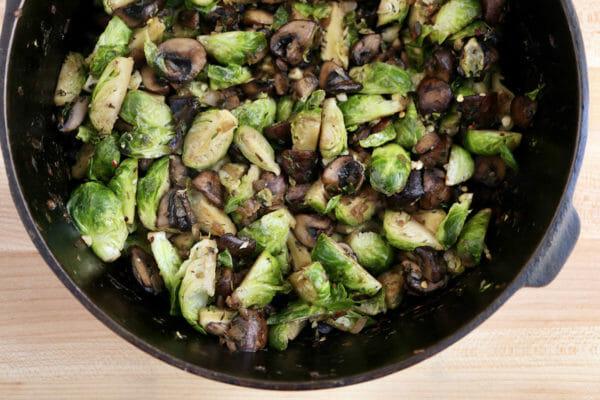 Брюссельская капуста и грибы, приготовленные в сковороде для приготовления овощной запеканки на завтрак.