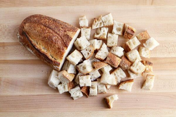 Хрустящий хлеб, который частично нарезан кубиками, чтобы приготовить вегетарианскую запеканку для завтрака. с козьим сыром.