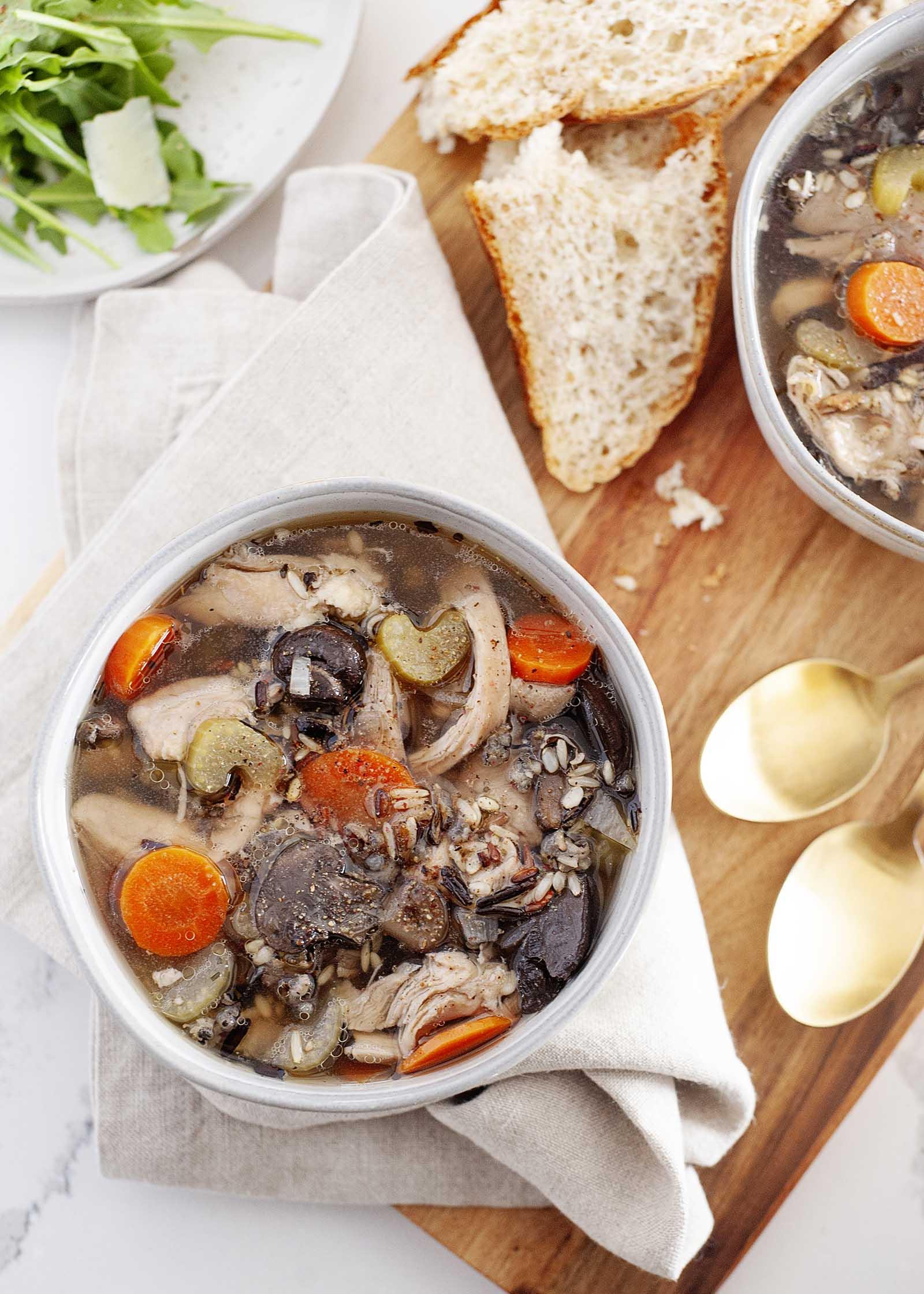 Чаша курино-рисового супа с ложками, хлебом и второй миской.