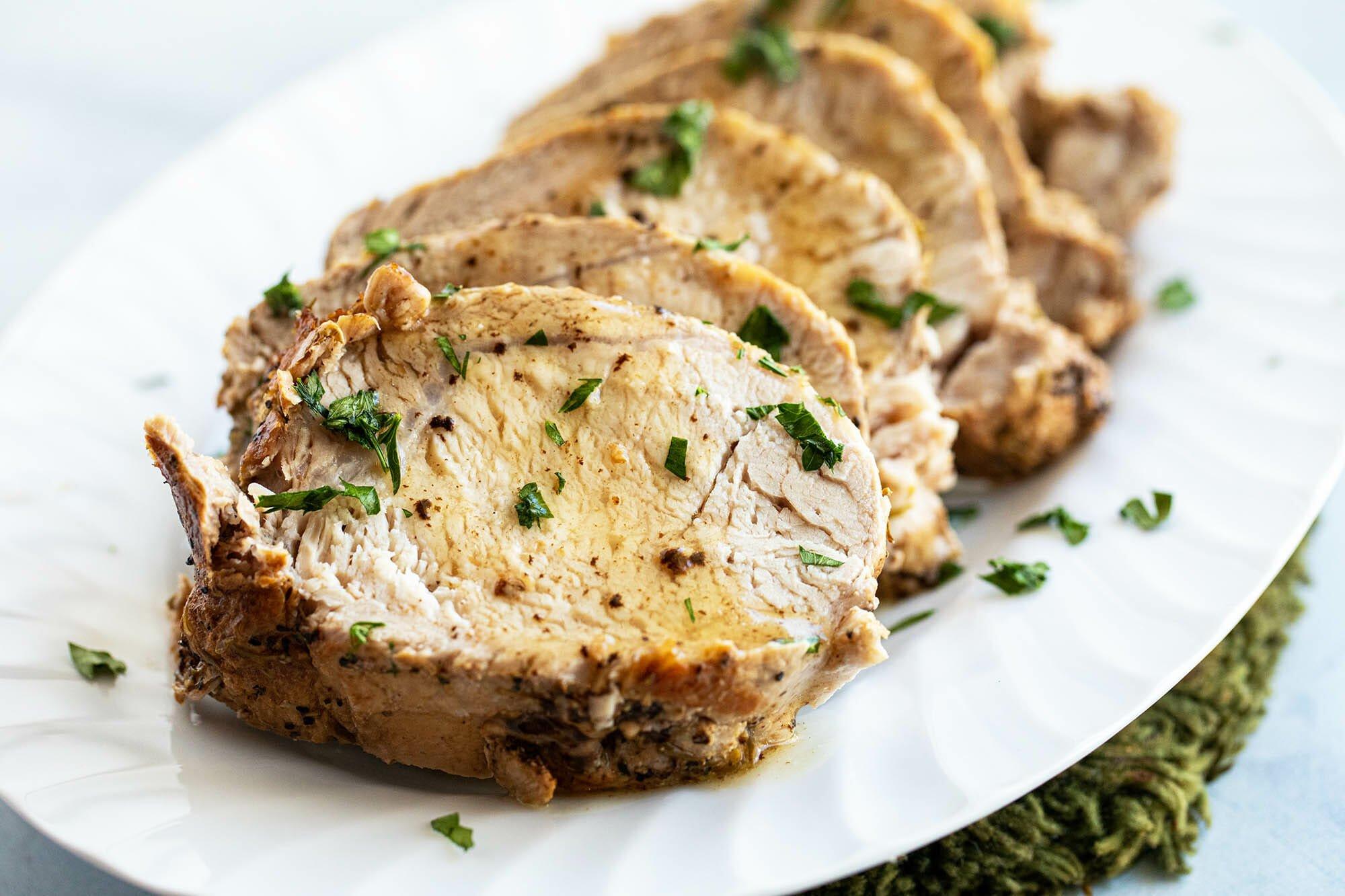 Толстые ломтики легкой свинины нарезаны на блюде. 