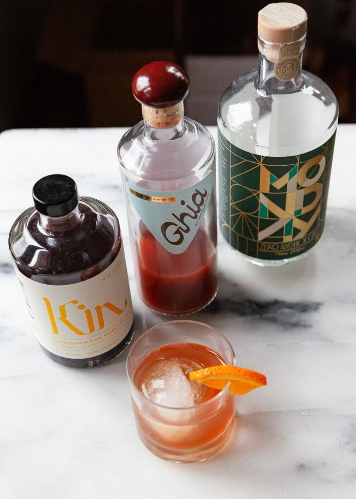 Три бутылки безалкогольных спиртных напитков и коктейль на столе.