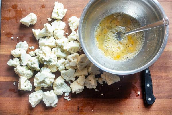 Металлическая миска с яйцом и приправами, смешанная вилкой и поставленная рядом с цветками цветной капусты, чтобы приготовить цветную капусту в воздушной фритюрнице с соусом буйвола.