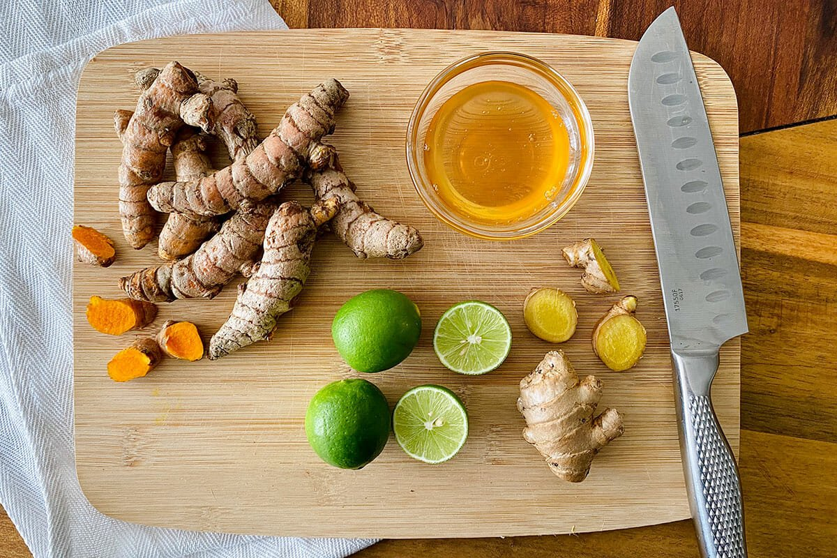 Лайм, имбирь, куркума и мед на разделочной доске, чтобы показать, как приготовить Джаму.