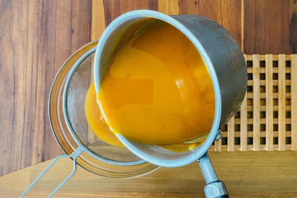 Переливание смеси куркумы и имбиря через сито для приготовления домашнего джаму.