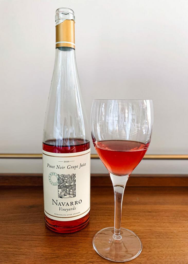 Бутылка полупустой бутылки безалкогольного вина рядом со стаканом вина с нулевой пробой.