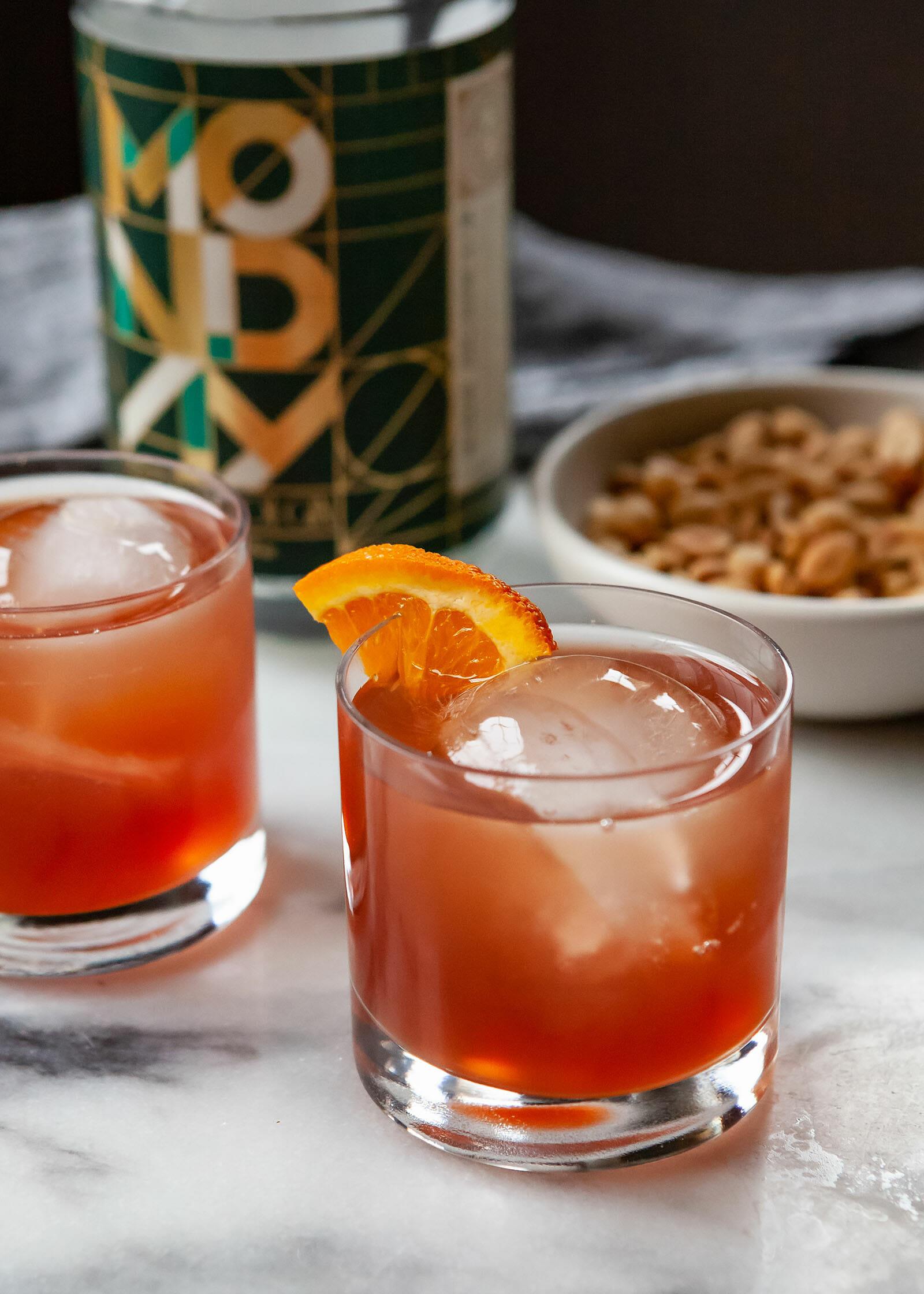 Безалкогольные негрони в бокале со льдом и долькой апельсина. Барные орехи и безалкогольный джин изображены за стеклом.