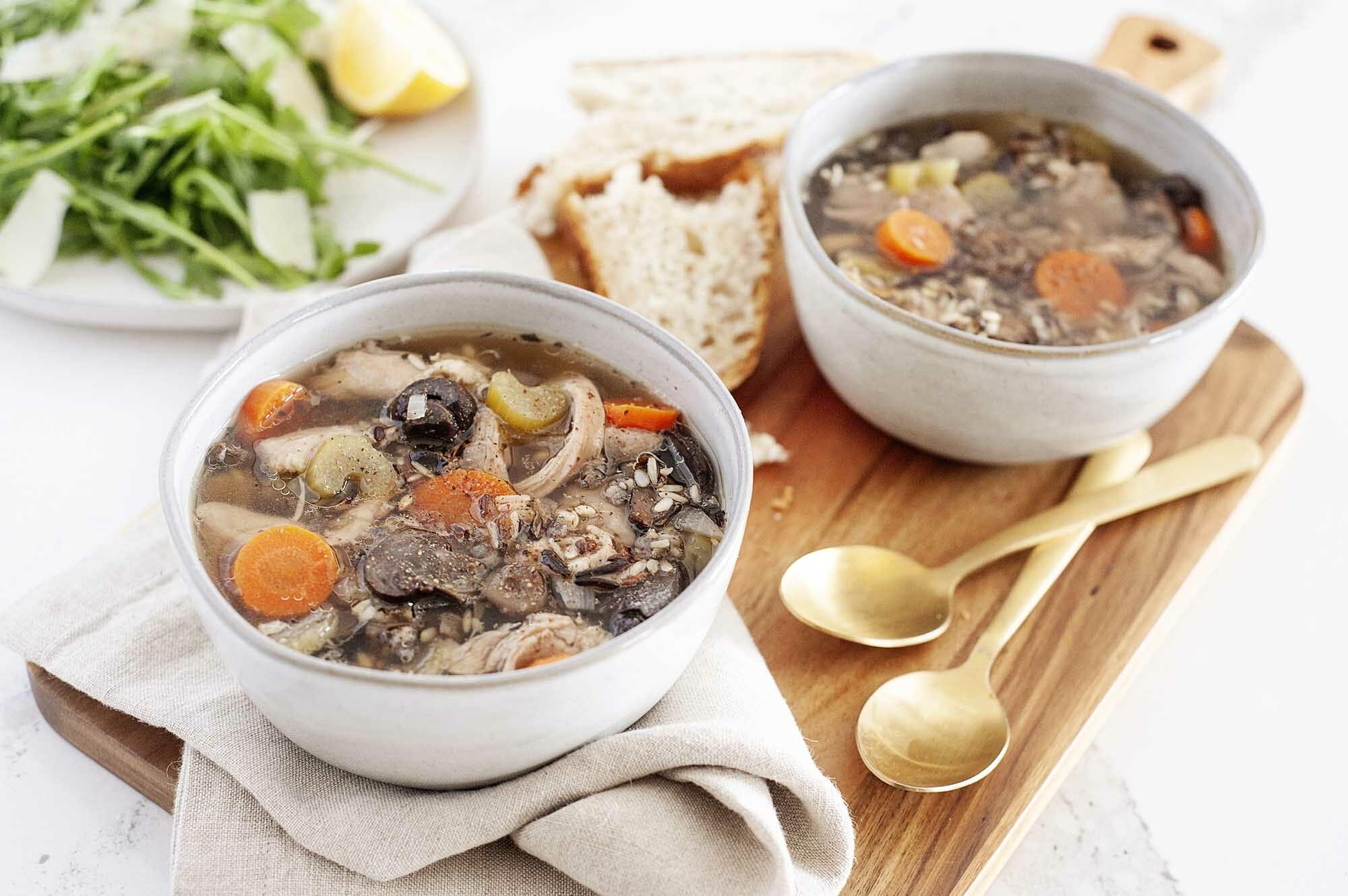 Две чашки легкого куриного и рисового супа с ложками, хлебом и салатом.