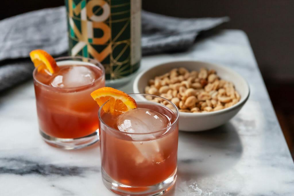 Два безалкогольных негрони в каменных стаканах с апельсиновой долькой и батончиками.
