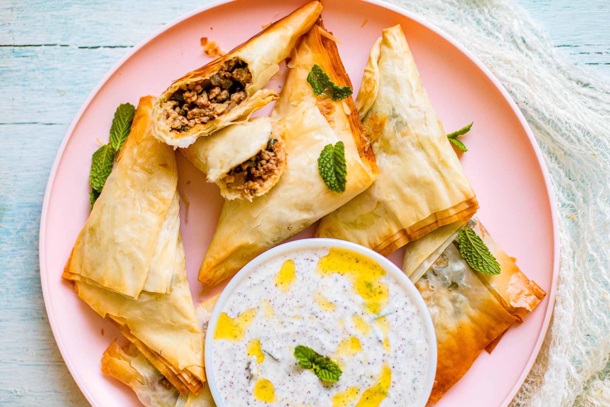 Запеченный индийский цыпленок Самоса Тикки Масала, сложенная в треугольник с мятным йогуртовым соусом на розовой тарелке с одной сломанной самосой.