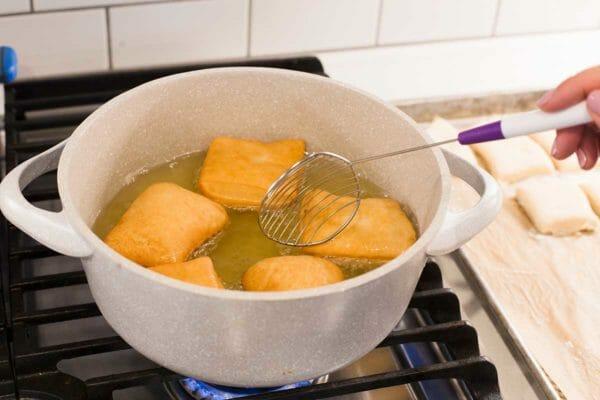 Бенье из Нового Орлеана готовят в духовке. голландская духовка на плите превращается в раскаленное масло. Одна сторона золотисто-коричневая. Их переворачивают с помощью шумовки.