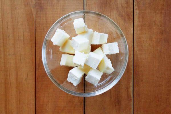 Нарезанное маслом кубики масла в небольшой стеклянной посуде и на деревянном столе.