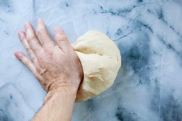 Рука замешивает тесто для королевского торта. на мраморном фоне.