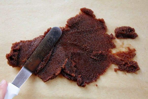 Смещенная лопатка намазывает начинку для кексов на тесто.