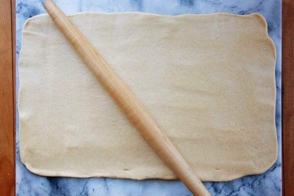 Легкое тесто для кекса раскатывается в большой прямоугольник. Сверху покоится скалка.