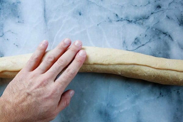 Лучшее тесто King Cake скатывается в форму трубы, положив руку на верх. Тесто лежит на мраморном фоне.