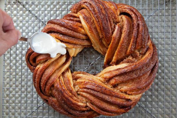 Ложка поливает глазурью самодельный золотисто-коричневый королевский торт, стоящий на охлаждающей решетке.